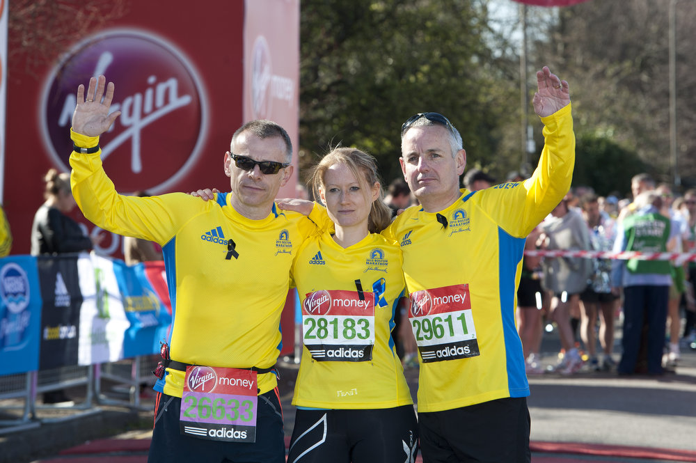 Description of . Boston Marathon participants  Kieth Luxon, Greg Smith and Tricia Bun pose for photographs ahead of the Virgin London Marathon 2013 on April 21, 2013 in London, England.  (Photo by Ben A. Pruchnie/Getty Images)