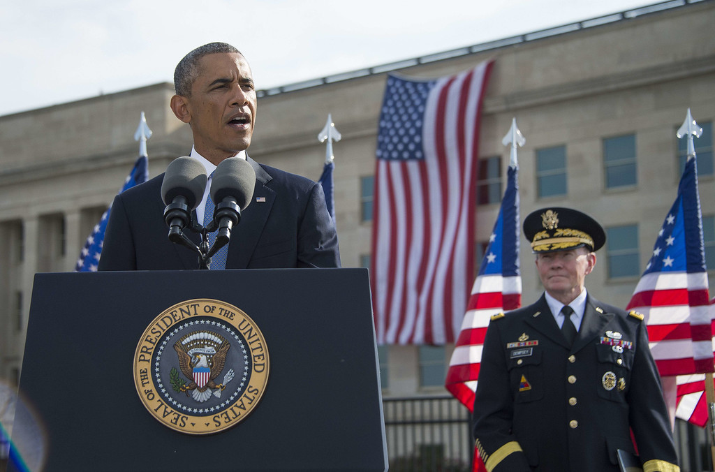 . US President Barack Obama speaks at the Pentagon in Washington, DC, September 11, 2014, during a ceremony marking the 13th anniversary of the 9/11 attacks on the United States with Chairman of the Joint Chiefs General Martin Dempsey (R). JIM WATSON/AFP/Getty Images