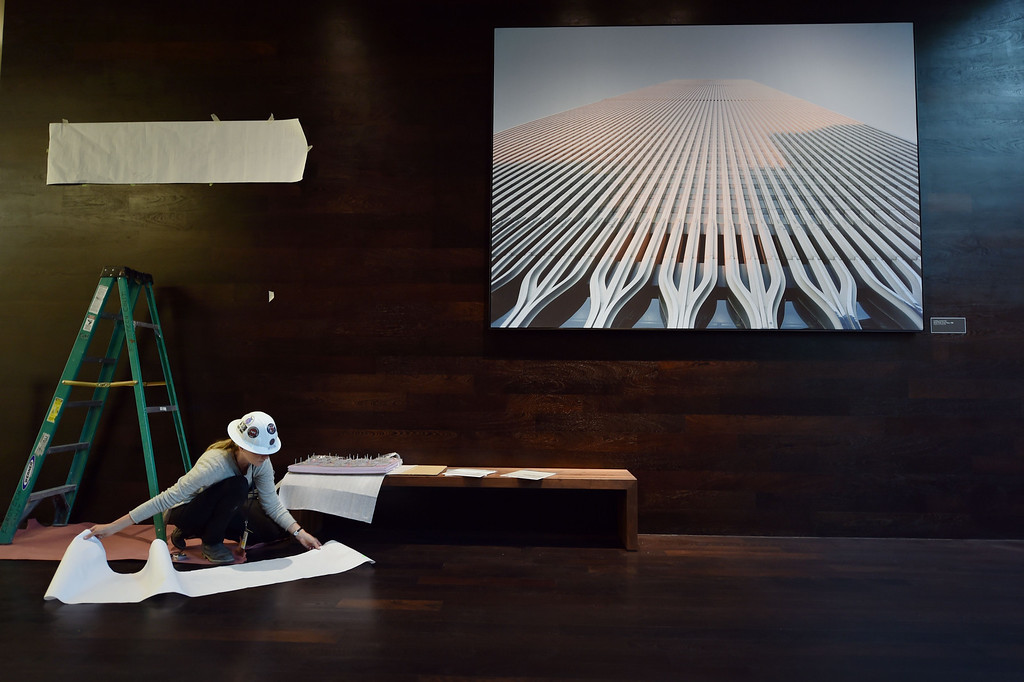 . A worker under a photograph of the World Trade Center seen during a press preview of the National September 11 Memorial Museum at the World Trade Center site May 14, 2014 in New York. AFP PHOTO/Stan HONDA/AFP/Getty Images