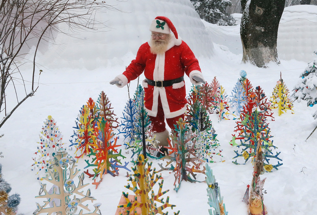 . A man dressed as Santa Claus walks in deep snow looking at small artificial Christmas trees in a snowy city park in Kiev, Ukraine, Tuesday, Jan. 10 2017. The temperature in Kiev is -6 degrees Centigrade (22 degrees Fahrenheit). (AP Photos/Efrem Lukatsky)