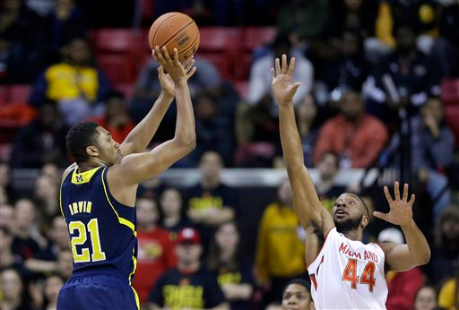 . Michigan guard/forward Zak Irvin, left, shoots over Maryland guard/forward Dez Wells in the second half of an NCAA college basketball game, Saturday, Feb. 28, 2015, in College Park, Md. (AP Photo/Patrick Semansky)