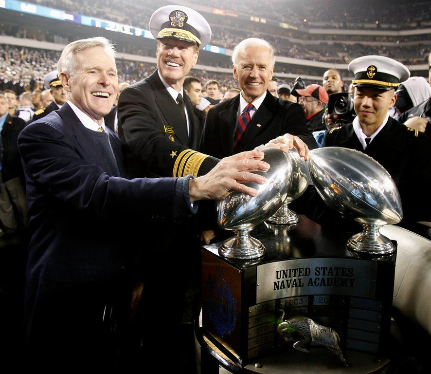 . U.S. Vice President Joe Biden (2nd R) presents the Commander in Chief\'s trophy to U.S. Naval academy superintendent Mike Miller (C) and Secretary of the Navy Ray Mabus (L), at the conclusion of the Army versus Navy NCAA football game in Philadelphia, Pennsylvania, December 8, 2012. REUTERS/Tim Shaffer