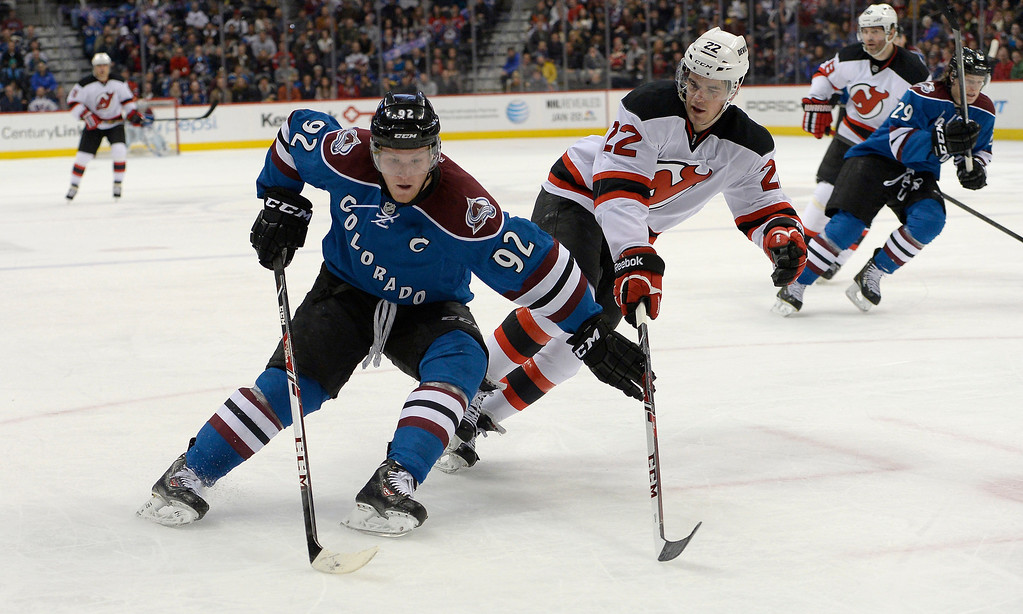 . Colorado Avalanche left wing Gabriel Landeskog (92) tries to hold off New Jersey Devils defenseman Eric Gelinas (22) as he skates in to the Jersey zone during the first period January 16, 2014 at Pepsi Center. (Photo by John Leyba/The Denver Post)