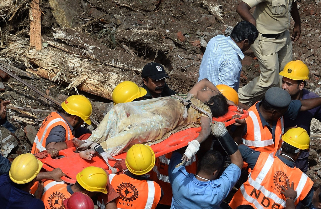 . Firefighters bring out a female survivor from the rubble at the site of a building collapse in Mumbai on September 27, 2013.  AFP PHOTO/Indranil  MUKHERJEE/AFP/Getty Images