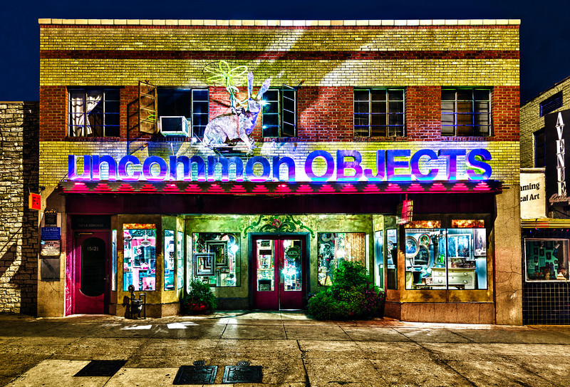 "Uncommon Objects is a collection of booths that sell vintage and eclectic art in the South Congress area known as SoCo in Austin Texas. The proprietor Steve Wiman describes Uncommon as ""Raw materials for creative living."" It is located about a mile south of Riverside drive in the heart of SoCo. There are many shops and places to grab a bite to eat nearby including a trailer park of different cuisines, Guero's Taco Bar and Homeslice Pizza to name a few. This shot was taken late Sunday night since that is the only time that cars are not parked in front of all the shops."
