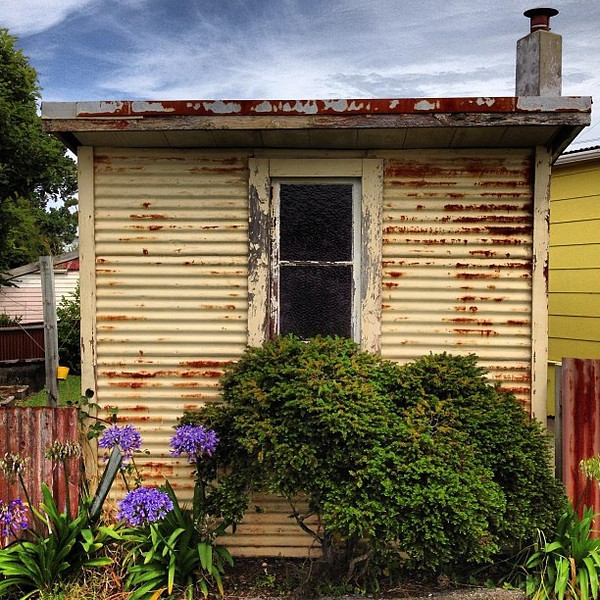 Colorful little love shack, New Zealand style. This tin roof is rusted.