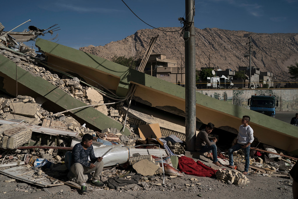 . People sit on the rubble of a destroyed house after an earthquake in the city of Darbandikhan, northern Iraq, Monday, Nov. 13, 2017. Authorities reported that a powerful 7.3 magnitude earthquake struck the Iraq-Iran border region on Monday and killed more than three hundred people in both countries, sent people fleeing their homes into the night and was felt far west as the Mediterranean coast. (AP Photo/Felipe Dana)
