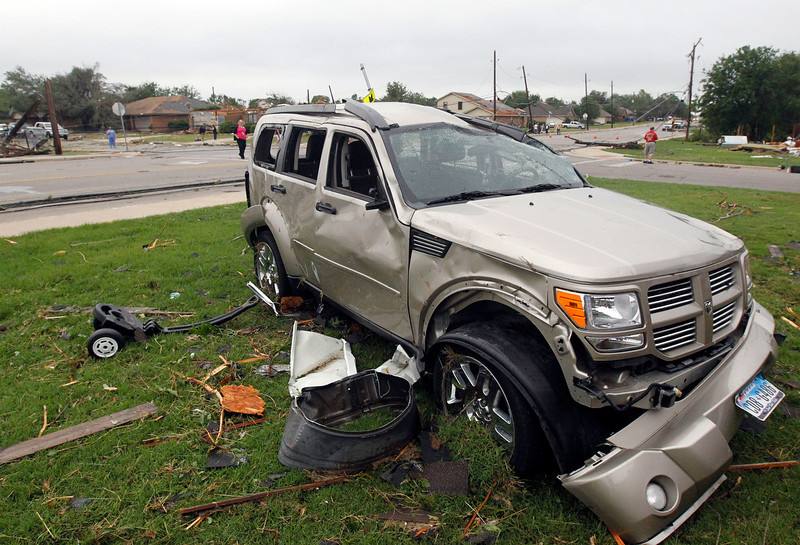 . Debris surrounds a damaged vehicle on Thursday, May 16, 2013, in Cleburne, Texas.  A rash of tornadoes slammed into several small communities in North Texas overnight, leaving at least six people dead, dozens more injured and hundreds homeless. The violent spring storm scattered bodies, flattened homes and threw trailers onto cars.  (AP Photo/The Dallas Morning News, Michael Ainsworth)