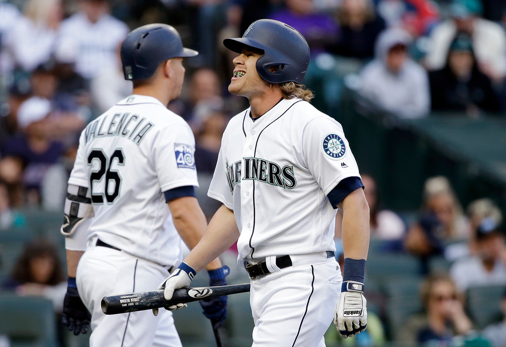 . Seattle Mariners\' Gordon Beckham, right, walks away from the plate after striking out against the Cleveland Indians in the eighth inning of a baseball game Saturday, Sept. 23, 2017, in Seattle. (AP Photo/Elaine Thompson)