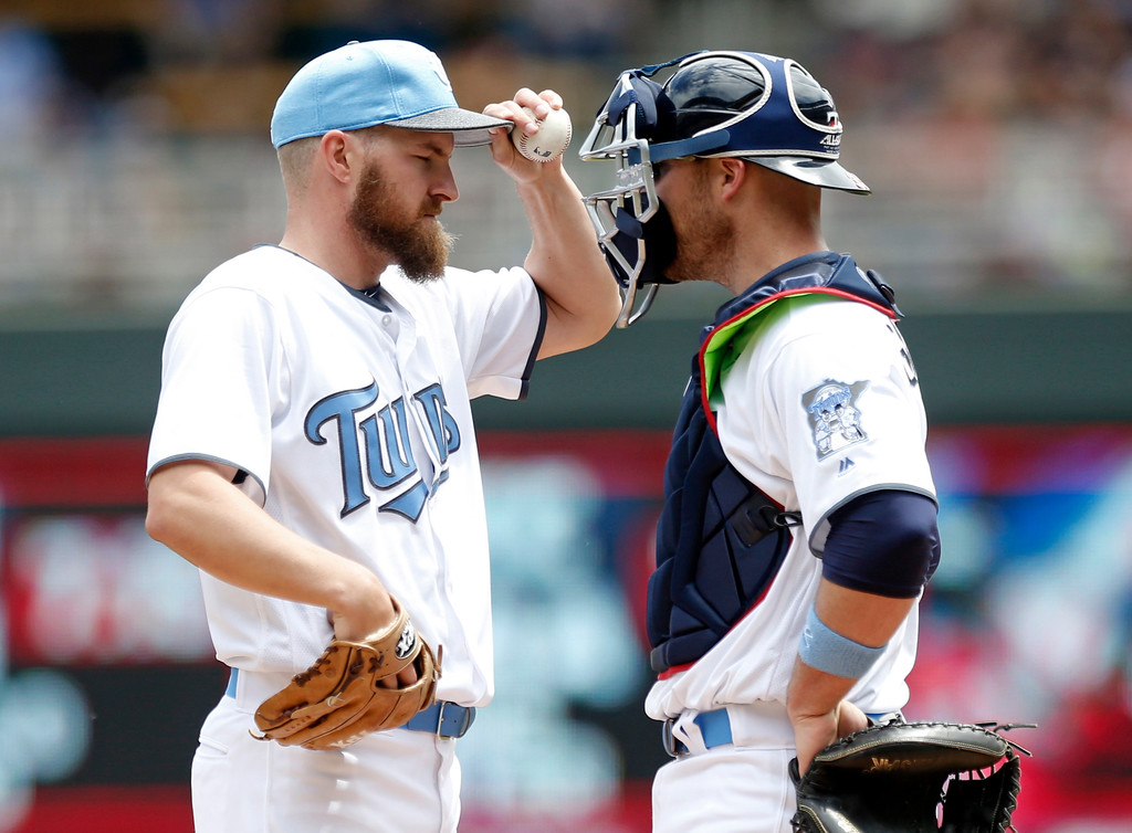 . Minnesota Twins\' Adam Wilk, left, has a chat with catcher Chris Gimenez in the first inning of a baseball game against the Cleveland Indians during game one of a baseball doubleheader Saturday, June 17, 2017, in Minneapolis. (AP Photo/Jim Mone)