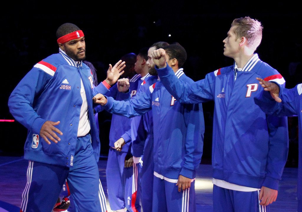 . Detroit Pistons\' Josh Smith, left, is greeted by teammates, including Jonas Jerebko, right, of Sweden, before the Pistons\' NBA basketball home opener against the Brooklyn Nets on Saturday, Nov. 1, 2014, in Auburn Hills, Mich. (AP Photo/Duane Burleson)