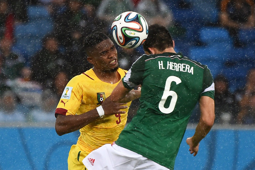 . Cameroon\'s forward and captain Samuel Eto\'o (L) fights for the ball with Mexico\'s midfielder Hector Herrera during a Group A football match between Mexico and Cameroon at the Dunas Arena in Natal during the 2014 FIFA World Cup on June 13, 2014. AFP PHOTO / CHRISTOPHE  SIMON/AFP/Getty Images