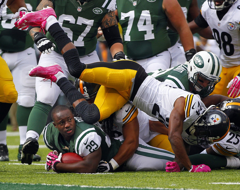 . Running back Bilal Powell #29 of the New York Jets is buried near the goal line by safety Troy Polamalu #43 and cornerback Ike Taylor #24 of the Pittsburgh Steelers in the first quarter during a game at MetLife Stadium on October 13, 2013 in East Rutherford, New Jersey. (Photo by Rich Schultz /Getty Images)