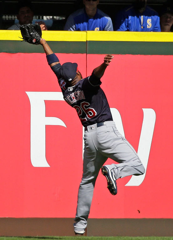. Cleveland Indians left fielder Austin Jackson makes a leaping catch to a ball hit by Seattle Mariners first baseman Yonder Alonso in the fourth inning of a baseball game, Sunday, Sept. 24, 2017, in Seattle. Jackson\'s throw to first base was in time to catch Mariners\' Kyle Seager off the base for a double play. (AP Photo/Ted S. Warren)