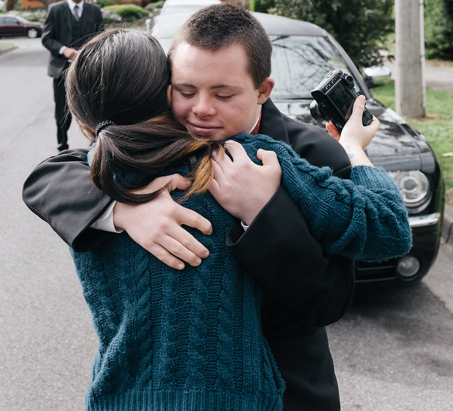 Young Man in Morning Suit in front of Limo hugging Sister