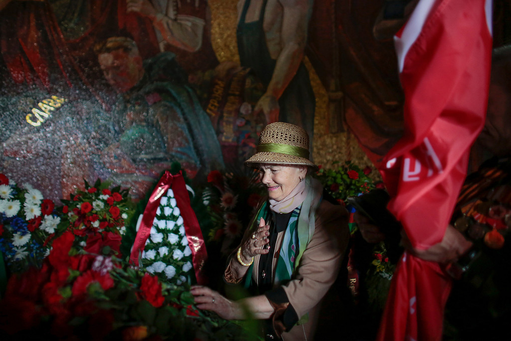 . A Russian veteran weeps as she lays down flowers during a wreath laying ceremony to celebrate the Victory Day at the Soviet War Memorial and military cemetery at the Treptower Park in Berlin, Germany, Friday, May 9, 2014. Hundreds of Russians attend the celebration in the German capital to mark the victory over Nazi-Germany. (AP Photo/Markus Schreiber)