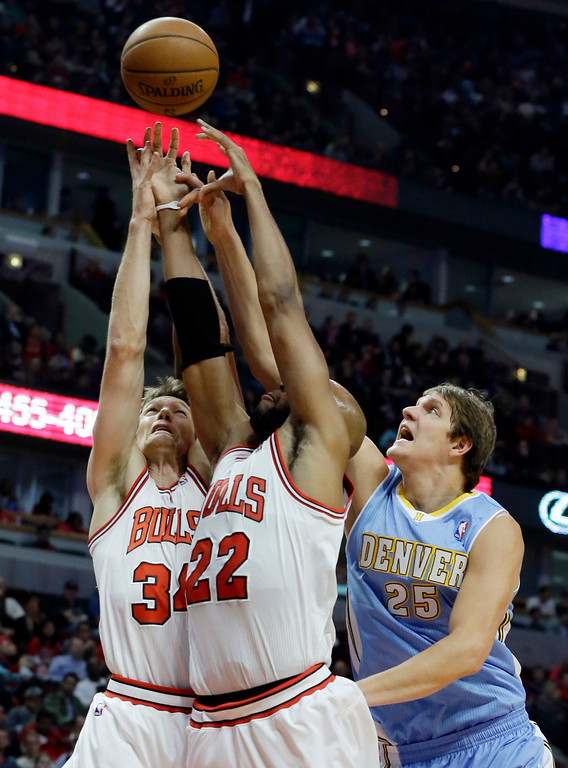 . Denver Nuggets center Timofey Mozgov (25) battle for a rebound against Chicago Bulls guard Mike Dunleavy, left, and Taj Gibson during the first half of an NBA preseason basketball game in Chicago on Friday, Oct. 25, 2013. (AP Photo/Nam Y. Huh)