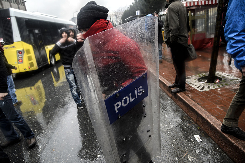 . A Turkish protester holds a police shield during clashes between riot police and demonstrators outside Okmeydani Hospital in Istanbul on March 11, 2014. Violent protests erupted between police and hundreds of protesters outside the hospital where 15-year-old Berkin Elvan, who had fallen into a coma after being hit by a tear gas canister during mass anti-government protests last year, died. (BULENT KILIC/AFP/Getty Images)