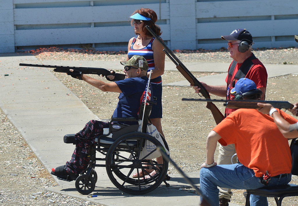 . Earl Batterton, of San Jose, an army Vietnam veteran, takes aim at a flying clay target, as his coach Dorothy Bayer, of Antioch, looks on  during the George Findly Memorial Disabled Veteran Trap Shoot at the Bay Point Rod and Gun Club in Concord, Calif., on Saturday, June 15, 2013. Each vet was assigned a mentor/coach from the club and each got to shoot two sets of flying clay targets. (Dan Rosenstrauch/Bay Area News Group)