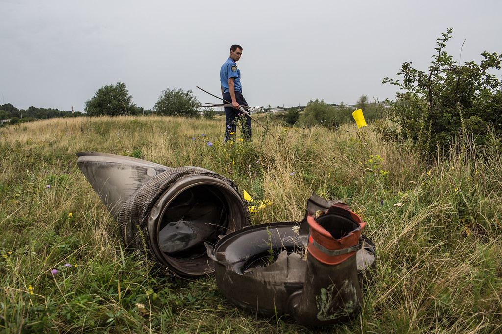. A Ukrainian police officer searches for human remains found in a field on July 18, 2014 in Grabovka, Ukraine. Air Malaysia flight MH17 traveling from Amsterdam to Kuala Lumpur crashed yesterday on the Ukraine/Russia border near the town of Shaktersk. The Boeing 777 was carrying 298 people including crew members, the majority of the passengers being Dutch nationals, believed to be at least 173, 44 Malaysians, 27 Australians, 12 Indonesians and 9 Britons.  (Photo by Brendan Hoffman/Getty Images)