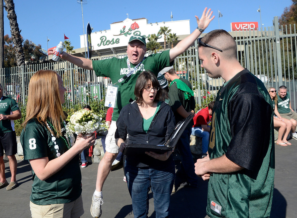 . A fan jumps behind as Julie Dove, center, marries Tom Mapley, right, a Michigan State University police officer and Elena Upperstrom prior to the 100th Rose bowl game in Pasadena, Calif., on Wednesday, Jan.1, 2014.   (Keith Birmingham Pasadena Star-News)