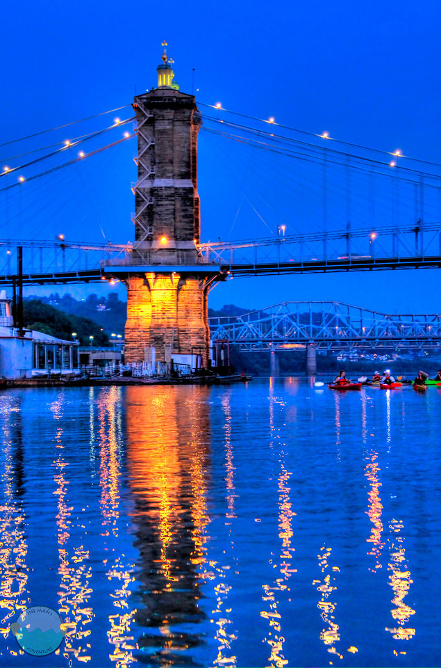 Suspension Tower<br /> The southern tower of teh two for the suspension bridge that spans between Covington, Kentucky and Cincinnati, Ohio with kayakers getting out for an early paddle.  I just loved the way the sky and water looked and the reflection at this exact moment during the pre dawn moments.