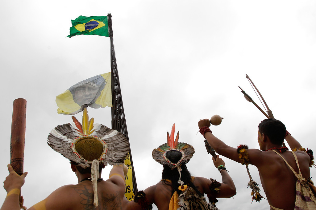 . Pataxo Indians watch a flag with the image of an Indian, raised by Greenpeace protesters, who were also on hand protesting against a proposed constitutional amendment which amends the rules for demarcation of indigenous lands in Brasilia, Brazil, Tuesday, Oct. 1, 2013. Greenpeace activists and Brazilian Indians gathered in their respective protests in the Brazilia\'s main square, marking the first day of the National Indigenous Mobilization protest against the constitutional amendment. (AP Photo/Eraldo Peres)
