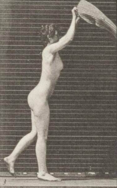 Nude woman spreading a rug on the floor