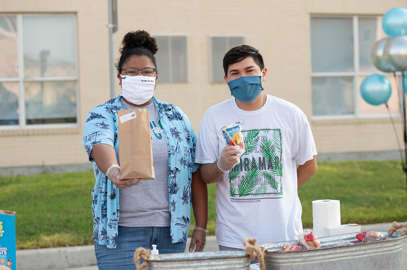 Ashley Granados (left) and Jorge Jimenez hand out breakfast items to students on the first day of the fall 2020 semester.