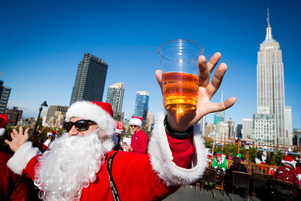 . A man dressed as Santa Claus holds a beer as he and others participate in SantaCon on a rooftop bar Saturday, Dec. 13, 2014, in New York.   SantaCon organizers retained lawyer Norman Siegel  last week as part of an effort to tame the excesses of the daylong party.  Siegel said the government cannot ban SantaCon. But he said the government can reasonably regulate the event. (AP Photo/John Minchillo)