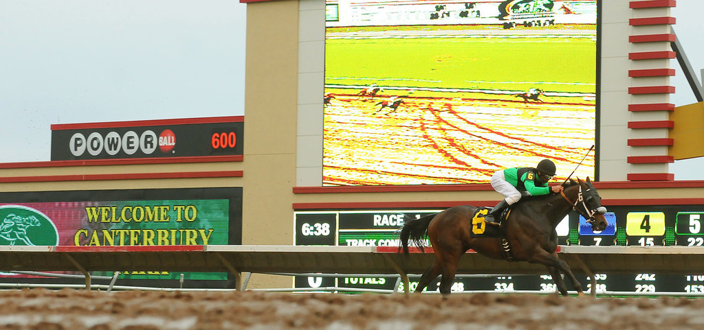 . Band of Silence, ridden by jockey Eddie Martin Jr., races past the new scoreboard in the infield to easily win the first race. (Pioneer Press: John Autey)