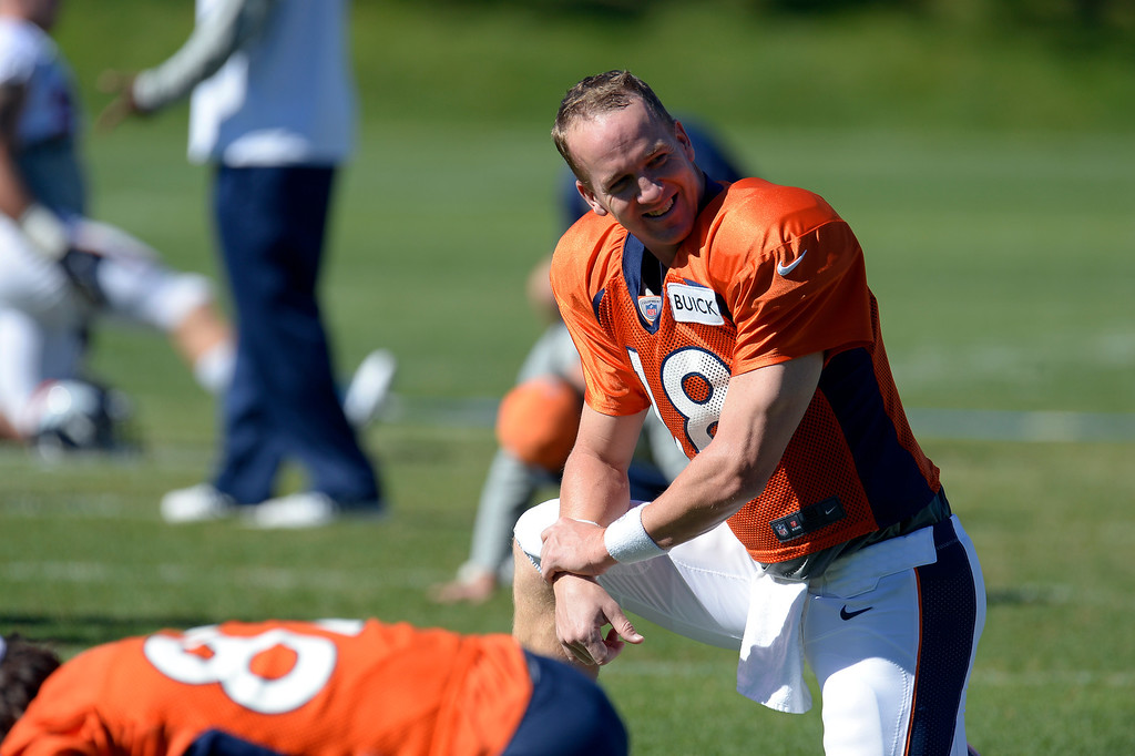 . Denver Broncos quarterback Peyton Manning (18) smiles as he stretches before practice October 2, 2013 at Dove Valley. (Photo by John Leyba/The Denver Post)