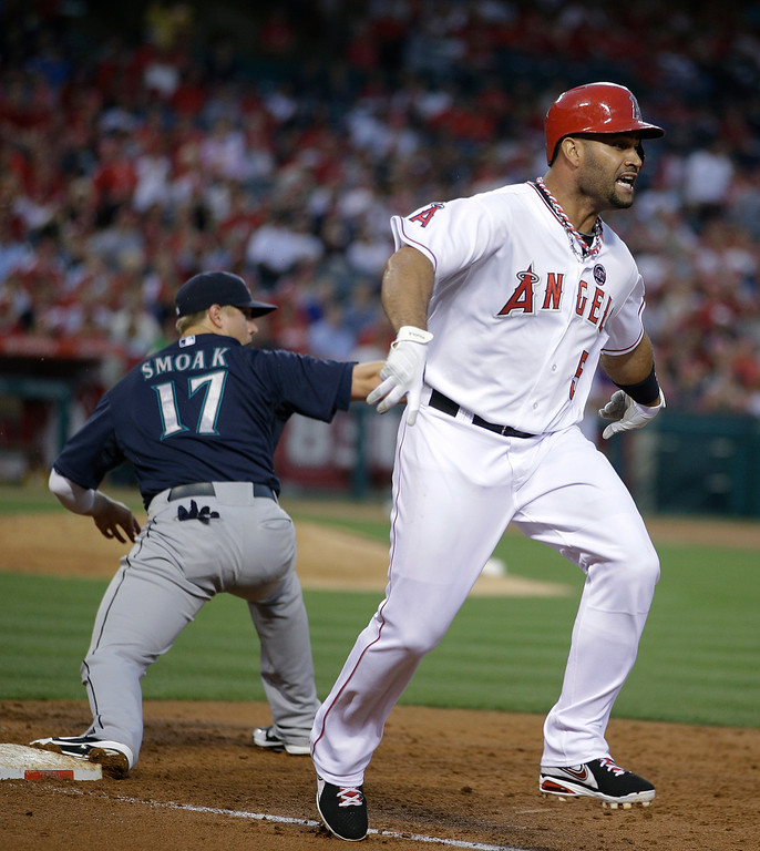 . Los Angeles Angels\' Albert Pujols, right, reacts after he was forced out by Seattle Mariners first baseman Justin Smoak during the third inning of a baseball game in Anaheim, Calif., Tuesday, June 18, 2013. (AP Photo/Jae C. Hong)