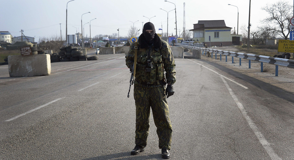 . A pro-Russian serviceman mans his position at the Chongar check point blocking the entrance to Crimea on March 7, 2014. Two buses carrying OSCE observers trying to enter Crimea turned back Friday after being blocked by armed men at a checkpoint, an AFP reporter said. Two sources within the mission said the team of 47 military and civilian observers was returning to the Ukrainian city of Kherson where they had spent the night after being similarly blocked on Thursday. ALEXANDER NEMENOV/AFP/Getty Images