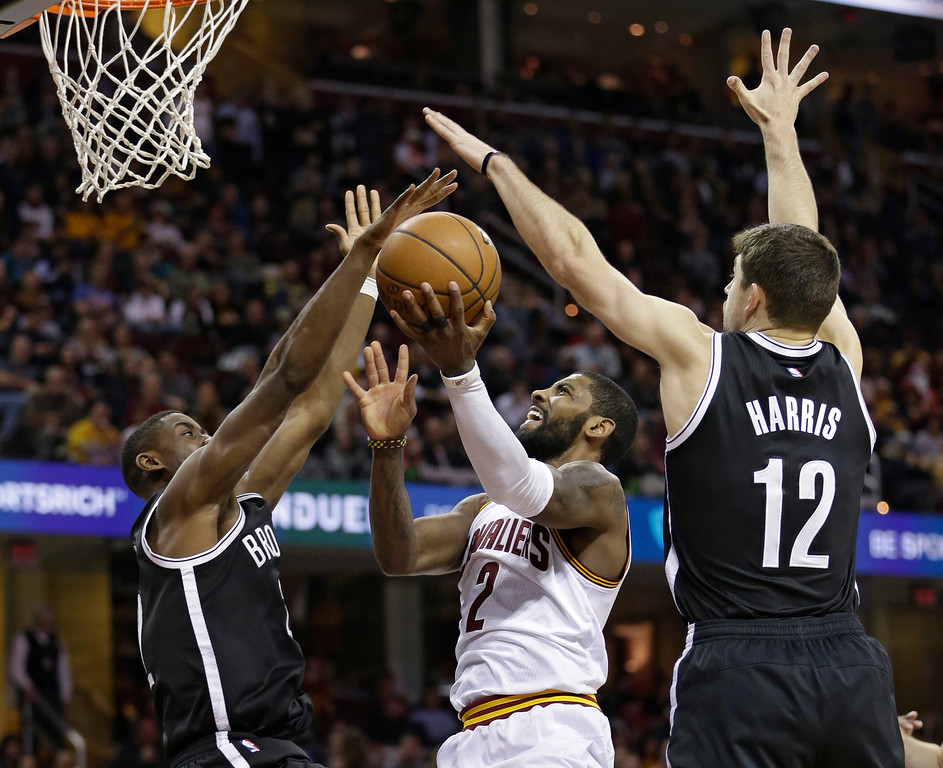 . Cleveland Cavaliers\' Kyrie Irving, center, drives against Brooklyn Nets\' Caris LeVert, left, and Joe Harris in the second half of an NBA basketball game, Friday, Dec. 23, 2016, in Cleveland. (AP Photo/Tony Dejak)