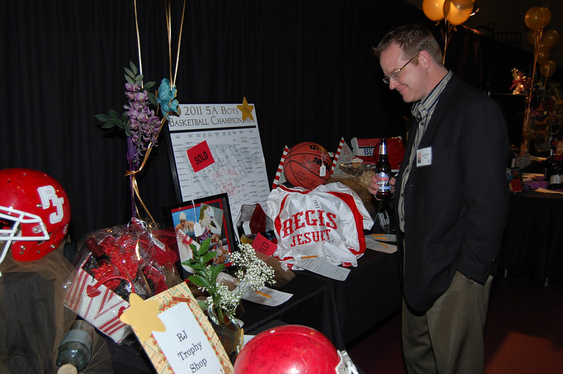"""Here I was able to use the RJ on the helmet, the RJ on the RJ Trophy Shop sign, and the """"REGIS JESUIT"""" just to the right and below the center of the frame, to make the Regis Jesuit brand stand out.  DSC_7367"""
