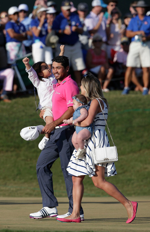 . Jason Day of Australia, walks off the 18th green with his family after winning The Players Championship golf tournament Sunday, May 15, 2016, in Ponte Vedra Beach, Fla.  Day is holding his son Dash as his wife Ellie holds Lucy. (AP Photo/Lynne Sladky)