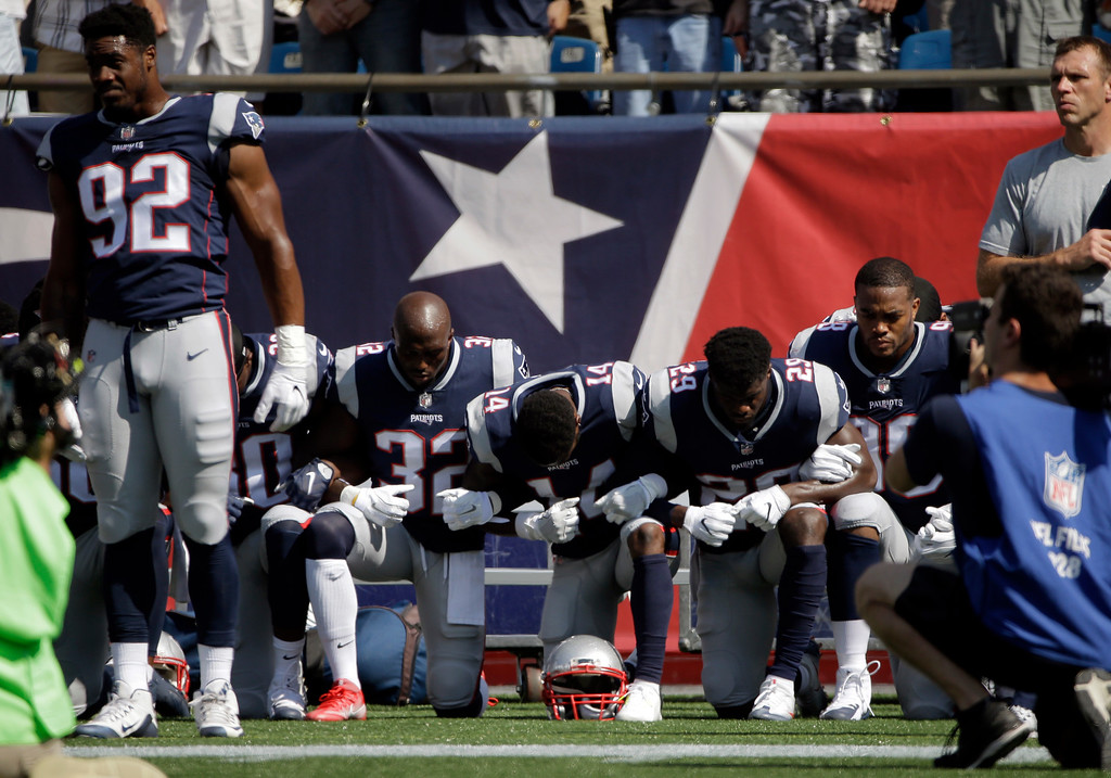 . Several New England Patriots players kneel during the national anthem before an NFL football game against the Houston Texans, Sunday, Sept. 24, 2017, in Foxborough, Mass. (AP Photo/Steven Senne)