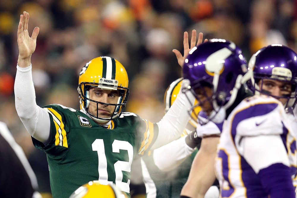 . Quarterback Aaron Rodgers #12 of the Green Bay Packers signals for a touchdown on a run by teamamte running back DuJuan Harris #26 in the first quarter against the Minnesota Vikings during the NFC Wild Card Playoff game at Lambeau Field on January 5, 2013 in Green Bay, Wisconsin. Harris was awarded a touchdown after the play was reviewed.  (Photo by Andy Lyons/Getty Images)