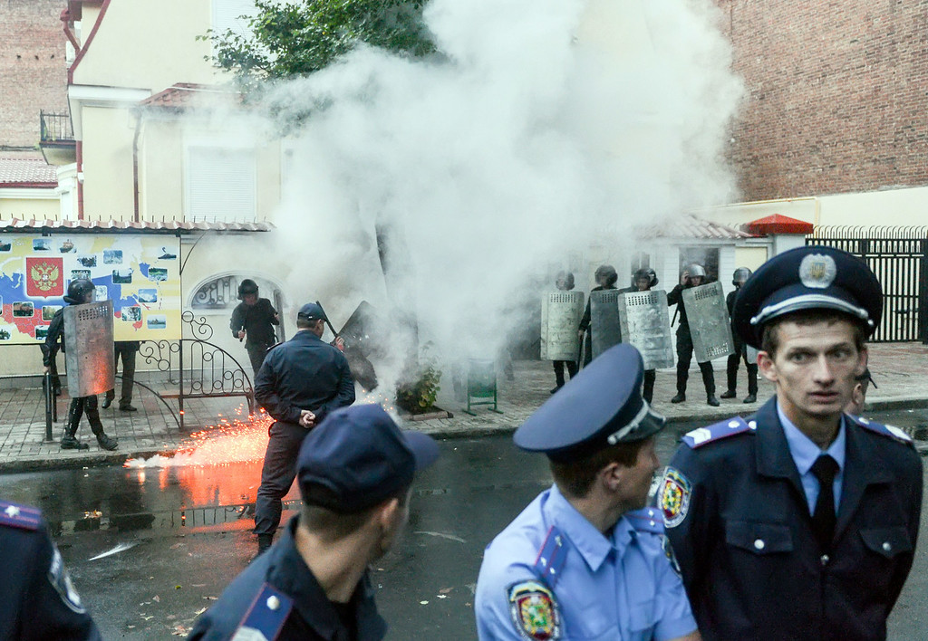 . Police  walk away as a protestor lights a smoke bomb during a demonstration outside the Russian Consulate in the southeastern Ukrainian city of Kharkiv on August 28, 2014. People called for a united Ukraine and asked Russia to withdraw its military forces from the country. Ukraine and the West said on August 28 that Russian troops were actively involved in the fighting tearing apart the east of the country, raising fears of a direct military confrontation between Kiev and its former Soviet master. The United States warned it was considering new sanctions against Russia over its involvement in the latest fighting in Ukraine. SERGEY BOBOK/AFP/Getty Images