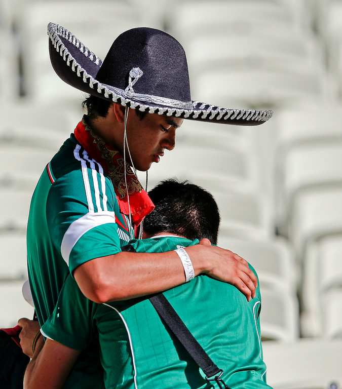 . Mexican supporters console each other after the Netherlands defeated Mexico 2-1 to advance to the quarterfinals during the World Cup round of 16 soccer match between the Netherlands and Mexico at the Arena Castelao in Fortaleza, Brazil, Sunday, June 29, 2014. (AP Photo/Eduardo Verdugo)