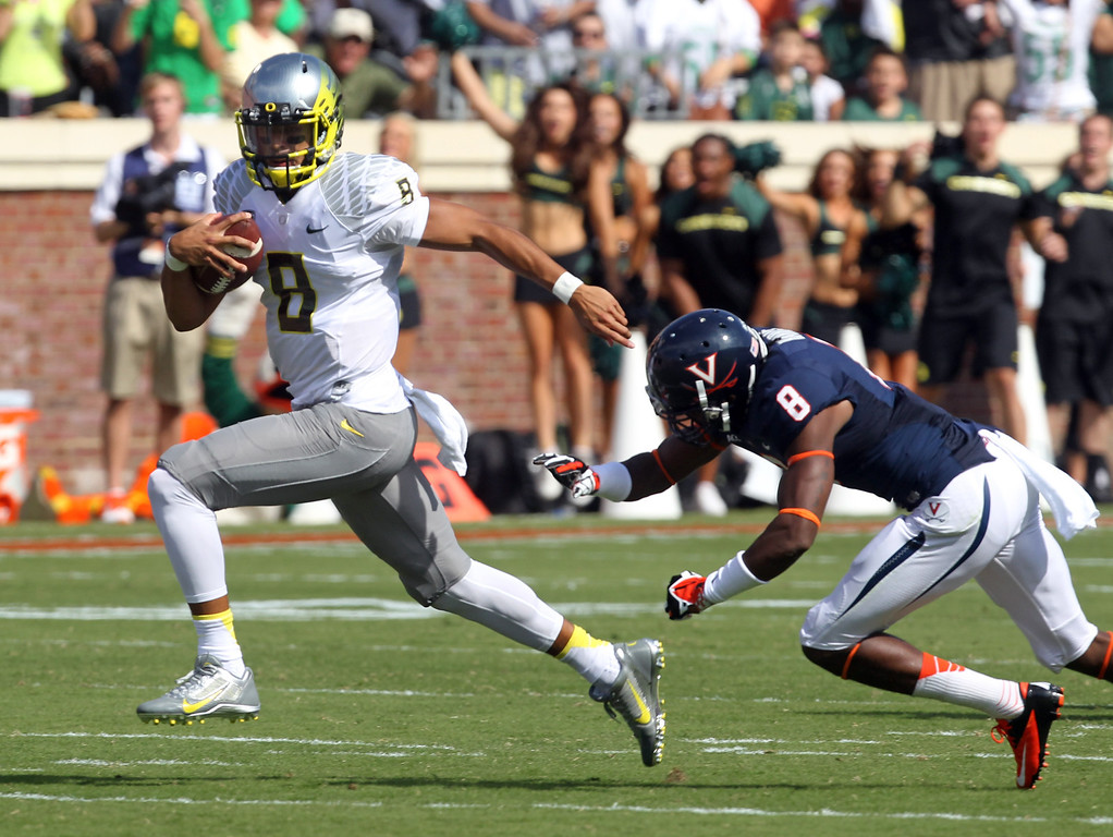 . Oregon quarterback Marcus Mariota (8) runs past Virginia safety Anthony Harris (8) for a touchdown during the first half of an NCAA college football game at Scott Stadium, Saturday, Sept. 7, 2013, in Charlottesville, Va. (AP Photo/Andrew Shurtleff)