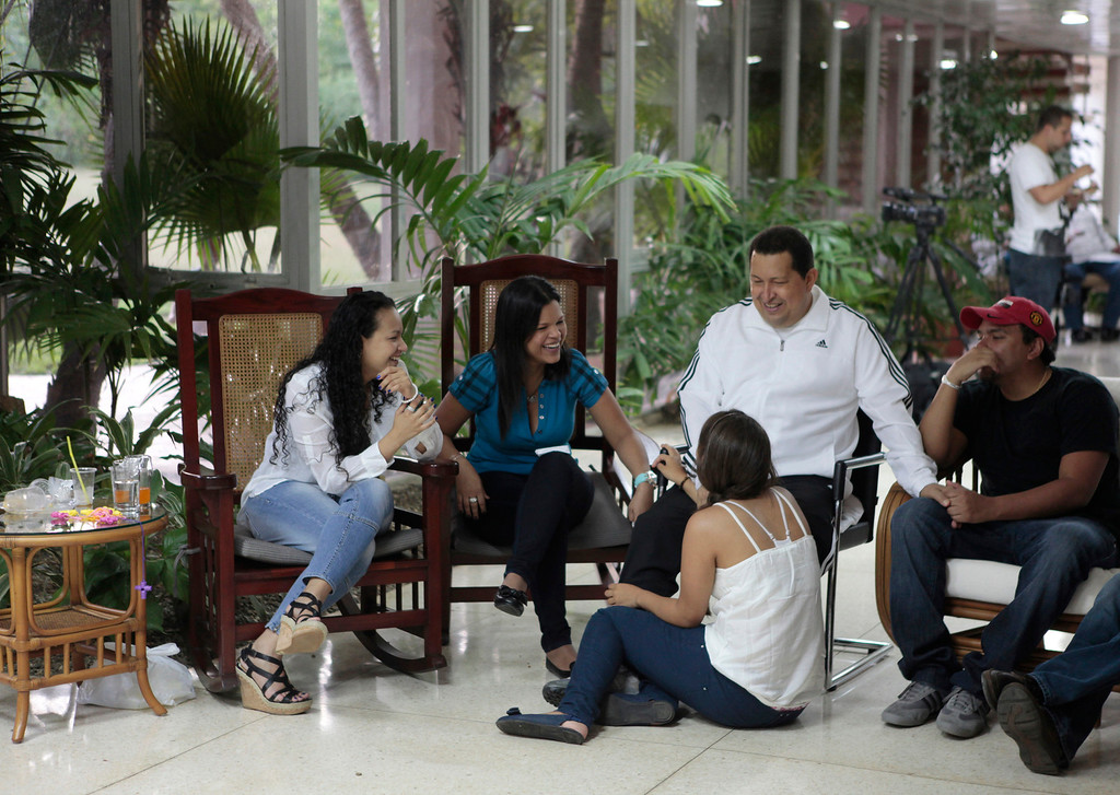. Venezuelan President Hugo Chavez (C) chats with his family while recovering in La Habana March 13, 2012. Chavez said he will return home from Cuba where he is recovering from cancer surgery next Sunday, to head up a re-election campaign.  REUTERS/Handout/Miraflores Palace