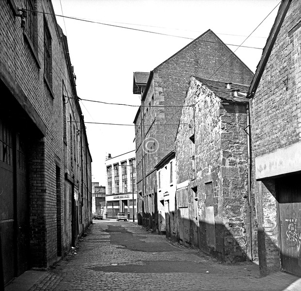 Carlton Court, looking west from S. Portland St.   The tall building was erected c1895 as stables for the Clyde Shipping Co., with wooden ramps at the back to give the horses access to the upper stalls, and a hoist at the front for raising feed to them. It has been renovated for use as offices.    April 1973