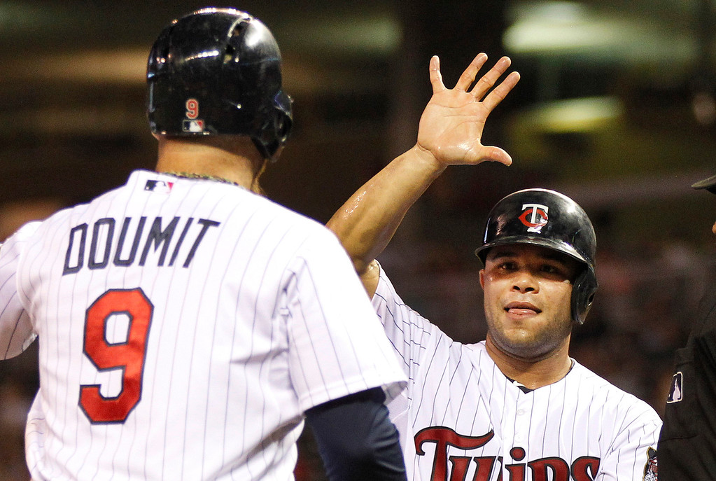 . Minnesota Twins catcher Josmil Pinto ,right, congratulates Ryan Doumit after Doumit scored in the fifth inning of their baseball game won by the Twins 6-3 in Minneapolis Monday, Sept. 9, 2013.(AP Photo/Andy Clayton-King)