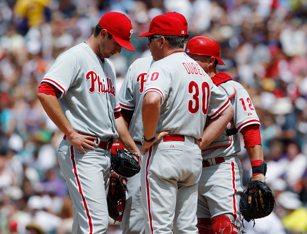 . Philadelphia Phillies starting pitcher Jonathan Pettibone, front left, confers with pitching coach Rich Dubee, front right, as first baseman Ryan Howard, back left, and catcher Humberto Quintero look on against the Colorado Rockies in the first inning of a baseball game in Denver, Saturday, June 15, 2013. Pettibone gave up six runs in the first inning. (AP Photo/David Zalubowski)