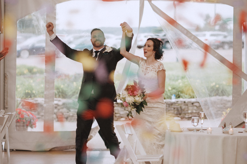 The bride and groom enter the reception in a hail of confetti.