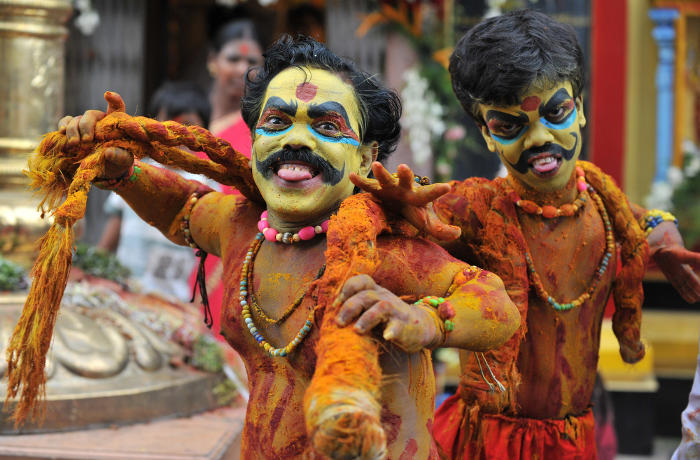 Description of . Indian dwarf artists Ashok and Vinay dressed up as Potharaju, the brother of Hindu Goddess of power, Mahakali, perform during the final procession of the eleven day traditional festival of 'Bonalu', a ritual offering to the goddes MahaKali at Sri Akkanna Madanna Mahankali Mandiran in Hyderabad, on July 25, 2011. The Goddess is honoured mostly by women during Bonalu festival by offerings of food and dancing. AFP PHOTO / Noah SEELAM