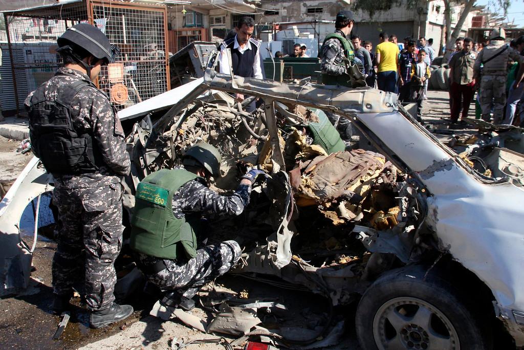 . Iraqi policemen examine the remains of a car bomb in Baghdad\'s Sadr City March 19, 2013.  REUTERS/Qahtan al-Sudani