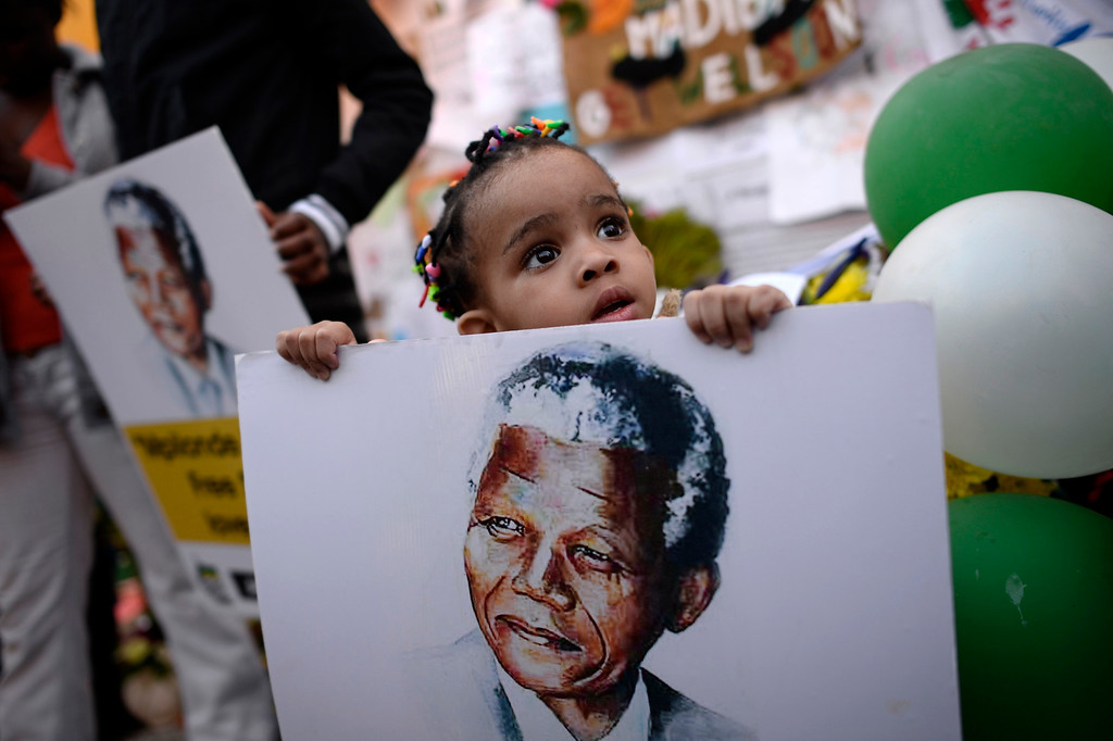 . Two-year-old Precious Mali holds a picture of former South African President Nelson Mandela as well-wishers gather outside the Medi-Clinic Heart Hospital where Mandela is being treated in Pretoria June 28, 2013. REUTERS/Dylan Martinez
